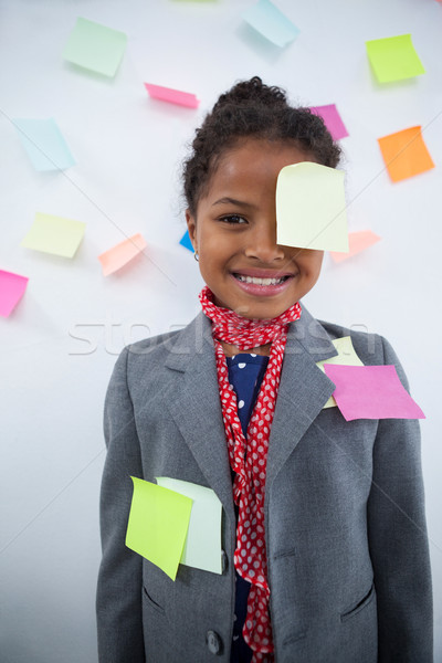 Happy businesswoman with sticky notes stuck on suit and head Stock photo © wavebreak_media