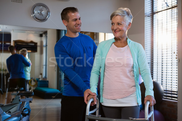 Physiotherapist assisting senior patient to walk with walking frame Stock photo © wavebreak_media