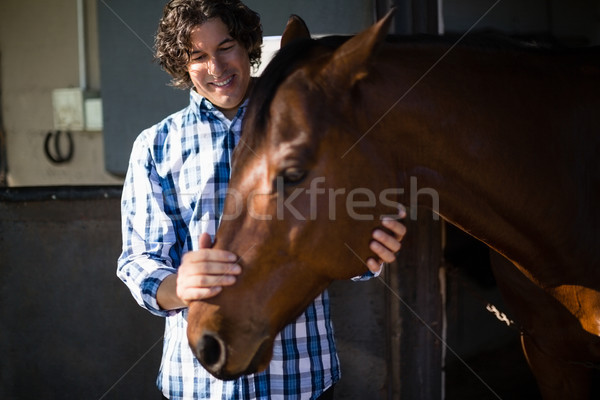 Man caressing the brown horse in the ranch Stock photo © wavebreak_media