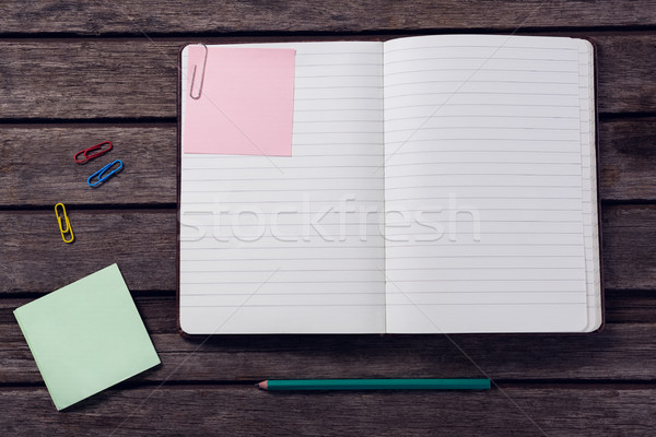 Overhead of diary, sticky notes, pencil and paper clip on wooden table Stock photo © wavebreak_media