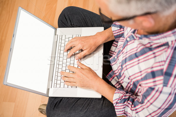 Casual man sitting and working with laptop Stock photo © wavebreak_media