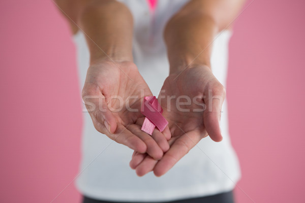 Mid section of young woman showing Breast Cancer Awareness ribbon Stock photo © wavebreak_media