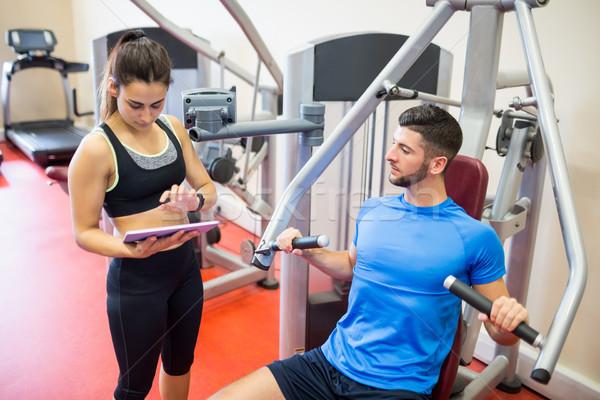 Ausbilder arbeiten Athleten Gewichte Maschine Fitnessstudio Stock foto © wavebreak_media