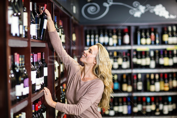 Smiling woman picking out bottle of wine  Stock photo © wavebreak_media