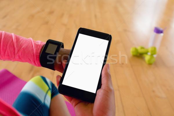 Woman holding mobile hone while using smartwatch Stock photo © wavebreak_media