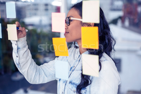 Asian femme écrit sticky notes verre mur Photo stock © wavebreak_media