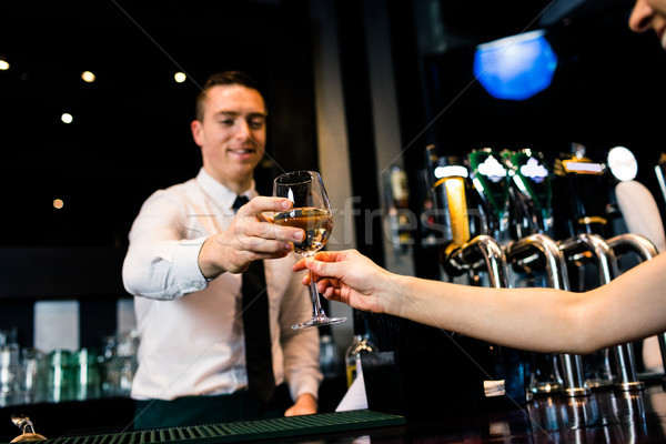 Stock photo: Smiling barman giving glass of white wine to client