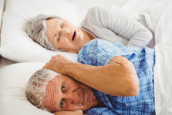 Senior man covering her ears while man snoring Stock photo © wavebreak_media