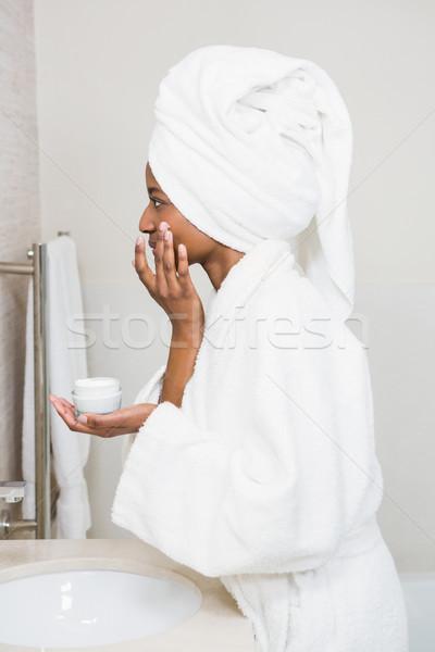 Young woman applying moisturizer Stock photo © wavebreak_media