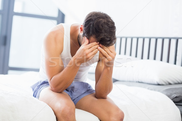 Tensed young man sitting on bed Stock photo © wavebreak_media