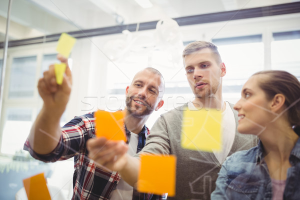 Business people sticking adhesive notes on window in office Stock photo © wavebreak_media