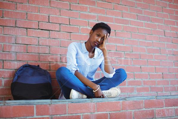 Triste écolière séance mur de briques école campus Photo stock © wavebreak_media