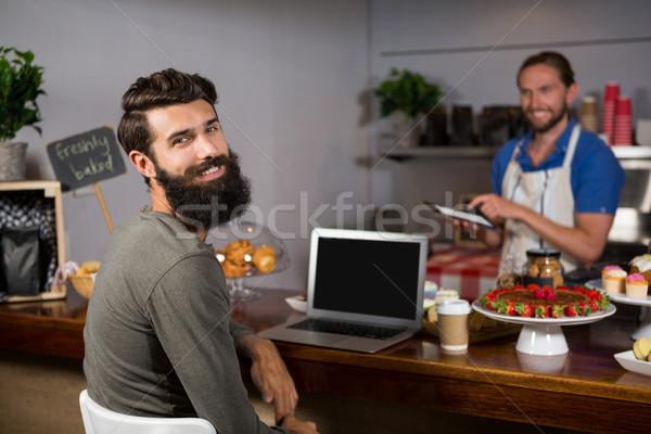 Maschio cliente utilizzando il computer portatile caffè counter coffee shop Foto d'archivio © wavebreak_media