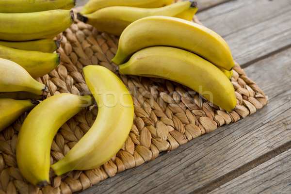 Bananas kept on placemat on wooden table Stock photo © wavebreak_media