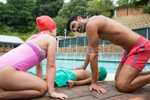 Lifeguard assisting unconscious boy while interacting with girl Stock photo © wavebreak_media