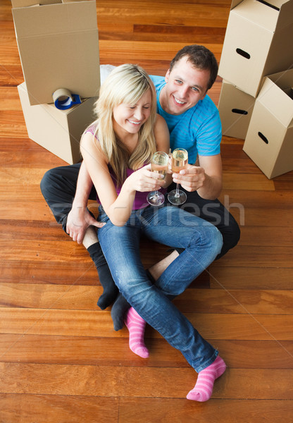Happy lovers moving house and drinking champagne Stock photo © wavebreak_media