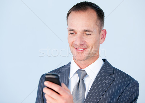 Handsome businessman sending a text with his  phone  Stock photo © wavebreak_media