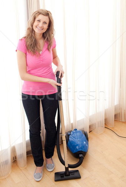 Stock photo: Portrait of a happy woman vacuuming