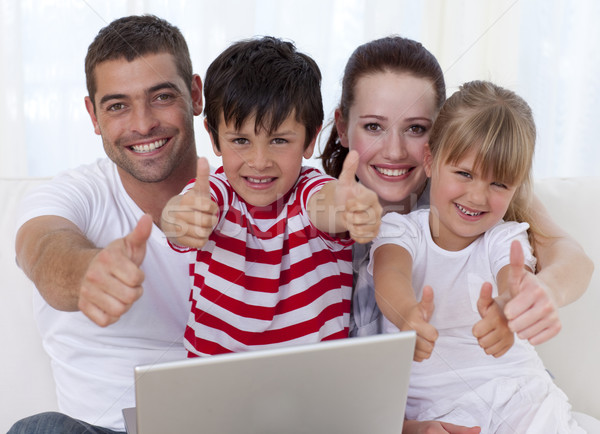 Happy family at home using a laptop with thumbs up Stock photo © wavebreak_media