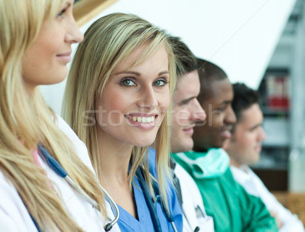 Portrait of female doctor smiling at the camera with her team in a line on stairs Stock photo © wavebreak_media