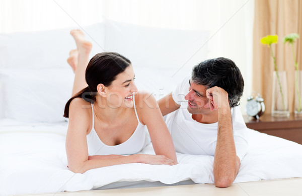 Happy affectionate couple interacting lying on their bed Stock photo © wavebreak_media