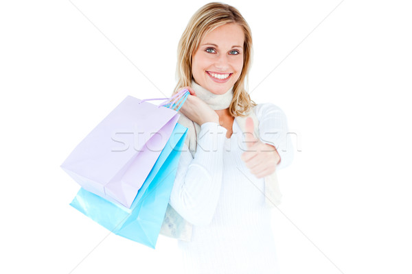 Positive woman with shopping bags and thumb up against white background Stock photo © wavebreak_media