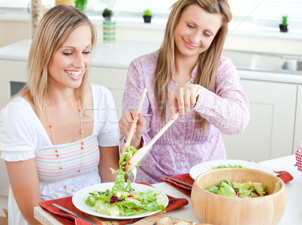 Two delighted women eating salad in the kitchen Stock photo © wavebreak_media