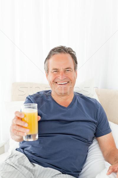 Emeryturę człowiek patrząc kamery pitnej soku Zdjęcia stock © wavebreak_media