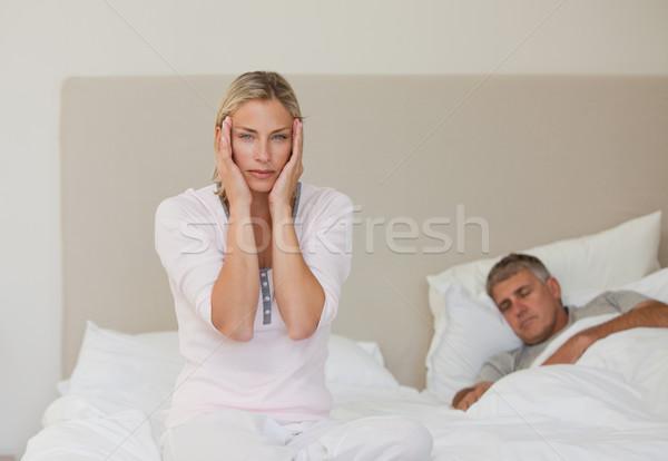 Stock photo: Woman having a headache while her husband is sleeping