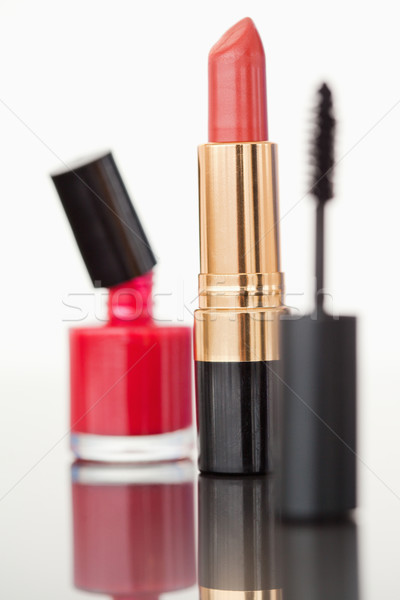 A mascara tube with a pale red lipstick and a nail polish flask against a white background Stock photo © wavebreak_media
