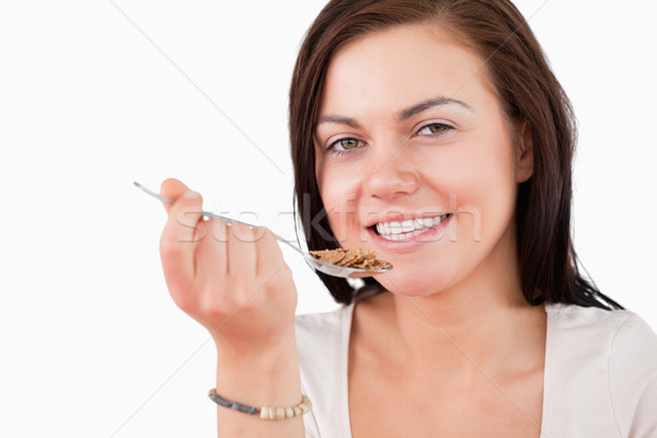 Close up of a smiling woman eating cereal while looking at the camera Stock photo © wavebreak_media