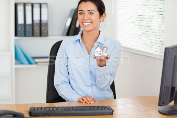 Beautiful woman holding a miniature house while looking at the camera at the office Stock photo © wavebreak_media