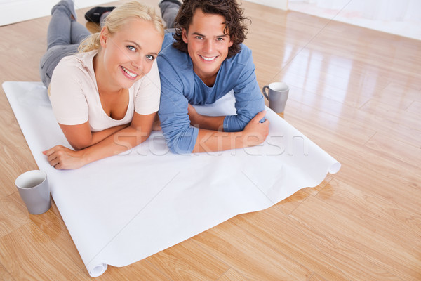 Close up of a couple with cups of coffee and a plan lying on the floor Stock photo © wavebreak_media