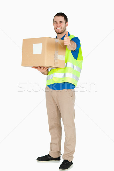 Smiling young delivery man giving approval while holding a parcel against a white background Stock photo © wavebreak_media