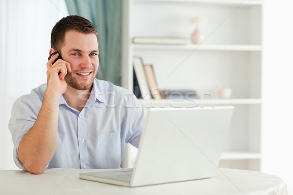 Smiling young businessman on the phone in his homeoffice Stock photo © wavebreak_media