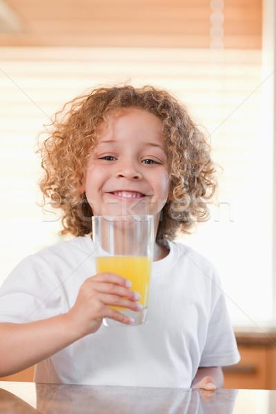 Smiling young girl having orange juice in the kitchen Stock photo © wavebreak_media
