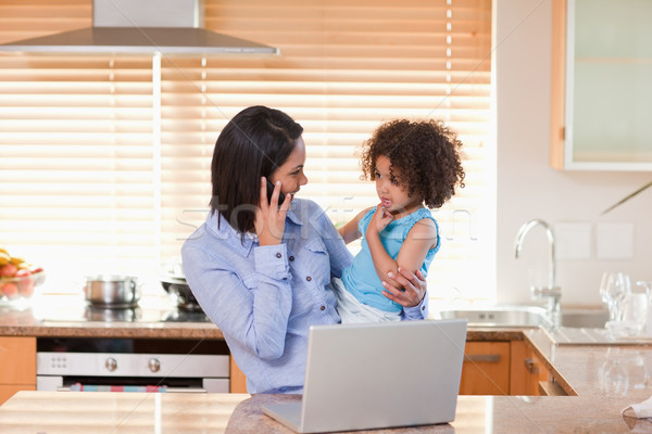 Young mother and daughter with cellphone and notebook in the kitchen together Stock photo © wavebreak_media