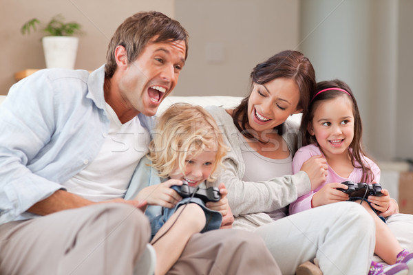 Laughing family playing video games in a living room Stock photo © wavebreak_media