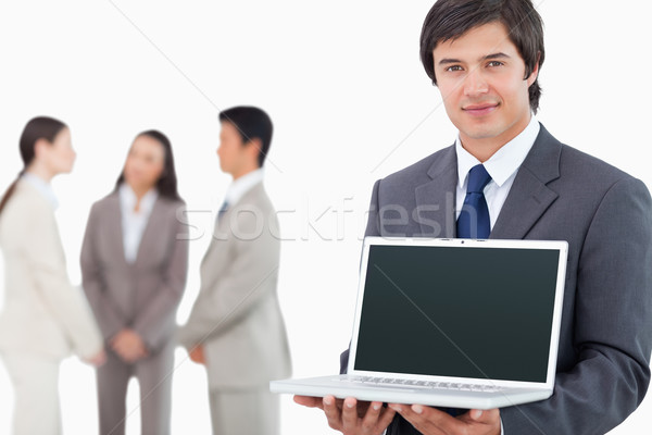 Salesman showing laptop screen with colleagues behind him against a white background Stock photo © wavebreak_media