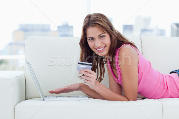 Young woman showing a beaming smile while holding a grey credit card Stock photo © wavebreak_media