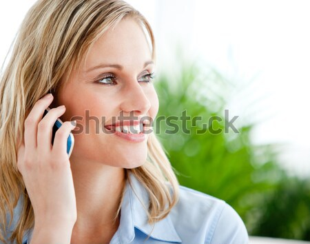 Young laughing woman standing upright in a parkland while talking on the phone Stock photo © wavebreak_media