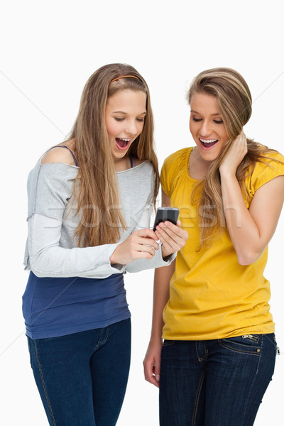 Two surprised students looking a cellphone screen against white background Stock photo © wavebreak_media