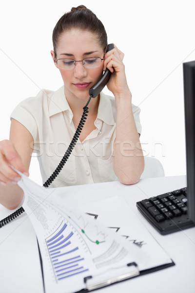 Portrait of a serious manager making a phone call while looking at statistics against a white backgr Stock photo © wavebreak_media