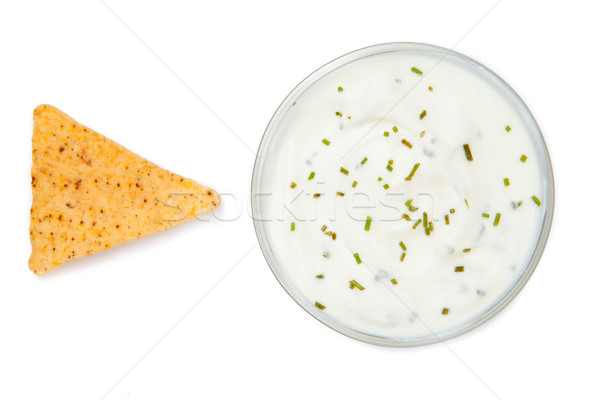 Bowl of dip with herbs beside a nacho against a white background Stock photo © wavebreak_media
