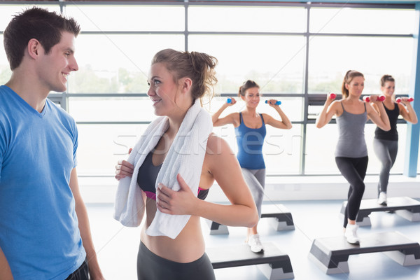 Aerobics class lifting weights while woman talking to trainer in gym Stock photo © wavebreak_media
