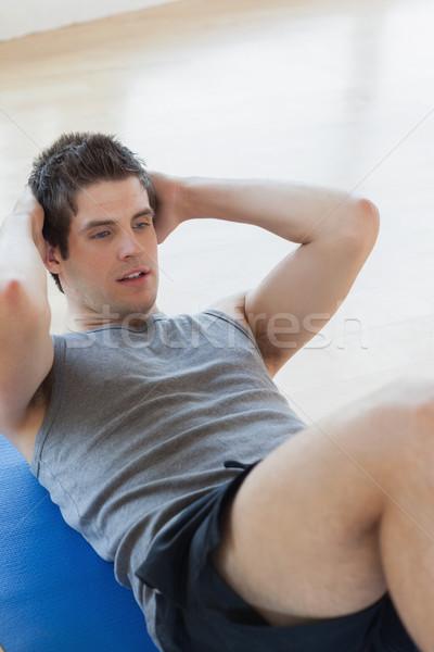 Man doing sit ups on the floor at the gym Stock photo © wavebreak_media