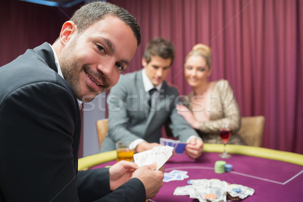 Man smiling and looking up from poker game in casino Stock photo © wavebreak_media