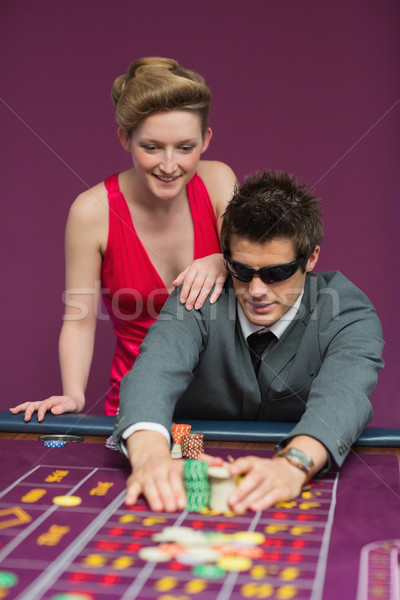 Stock photo: Man in sunglasses taking his winnings at roulette table