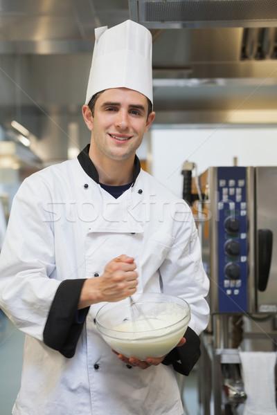 Cheerful man mixing batter in the kitchen Stock photo © wavebreak_media