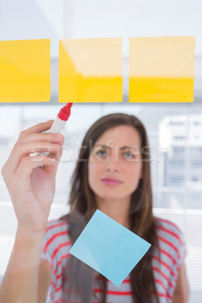 Young woman writing on sticky note Stock photo © wavebreak_media